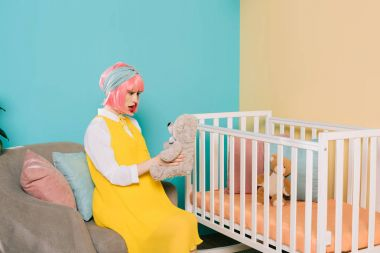 surprised retro styled pregnant pin up woman with pink hair sitting with teddy bear near baby cot in child room