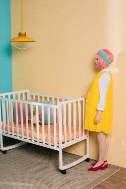 side view of retro styled pregnant pin up woman with pink hair standing near baby cot in child room
