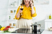 cropped image of woman talking by smartphone and drinking wine in kitchen