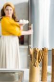 žena s deskou z lednice s dřevěné špachtle na popředí v kuchyni