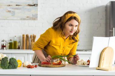 beautiful woman reading recipe in recipe book at kitchen