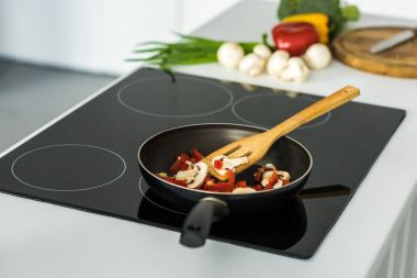 frying pan with appetizing vegetables on electric stove in kitchen