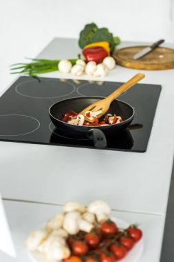 frying pan with vegetables on electric stove in kitchen