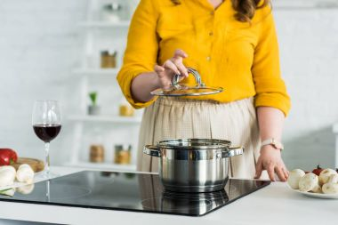 cropped image of woman holding lid from pan near electric stove in kitchen