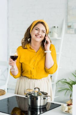 woman talking by smartphone and drinking wine in kitchen