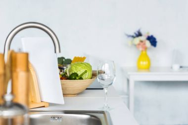 empty wineglass and vegetables near sink on kitchen counter