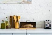 Fotografia pane nel granaio e tostapane sul bancone della cucina