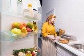 krásná žena krájení zeleniny v kuchyni s lednicí na popředí