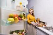 krásná žena, řezání zeleniny a při pohledu na fotoaparát v kuchyni