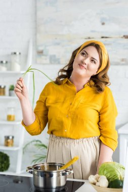 pensive beautiful woman holding green onion in kitchen