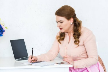 beautiful woman writing something to notebook in kitchen