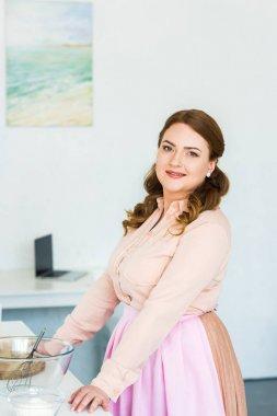 beautiful woman standing at kitchen counter and looking at camera