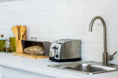 toaster, breadbasket with bread near sink in kitchen