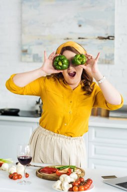 beautiful woman covering eyes with bell peppers at kitchen