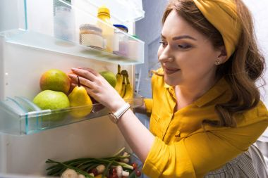 beautiful woman taking fruits from fridge at kitchen