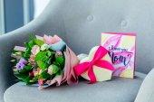 Fotografia Chiuda sulla vista di wrapping bouquet di fiori, regalo a forma di cuore e ti amo cartolina mamma sulla poltrona, concetto di giorno di madri