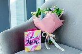 Fotografia Chiuda sulla vista di wrapping bouquet di fiori e ti amo cartolina dauguri mamma sulla poltrona, concetto di giorno di madri