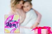Fotografia fuoco selettivo del io ti amo mamma cartolina, regalo incartato e che abbraccia la famiglia su priorità bassa
