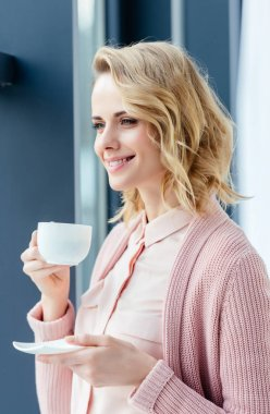side view of smiling thoughtful woman with cup of coffee