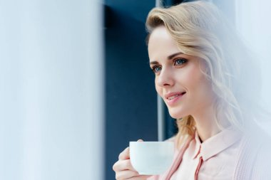 side view of thoughtful woman with cup of coffee looking away