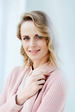 portrait of beautiful smiling woman in pink blouse and jacket looking at camera