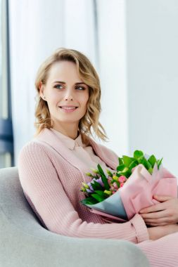 portrait of beautiful smiling woman with bouquet of flowers