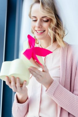 happy woman opening heart shaped gift box in hands, mothers day holiday concept
