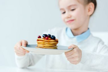selective focus of little kid looking at homemade pancakes with berries and honey in hands