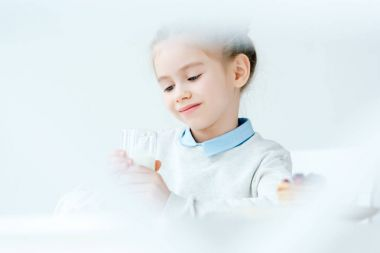 selective focus of cute smiling child looking at glass of milk in hands