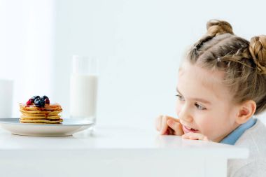 selective focus of little kid looking at homemade pancakes with berries, honey and glass of milk on table
