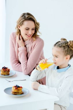 smiling mother and daughter having breakfast together at table