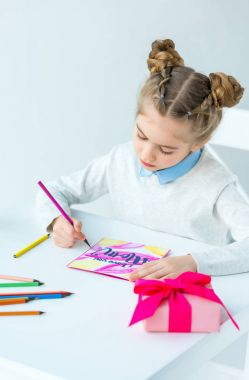 portrait of kid drawing greeting postcard for mother with colorful pencils at table, mothers day holiday concept