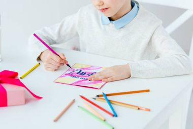 cropped shot of kid drawing greeting postcard for mother with colorful pencils at table, mothers day holiday concept