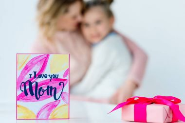 selective focus of i love you mom postcard, wrapped gift and hugging family on background