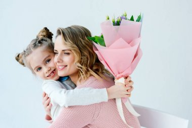 portrait of smiling daughter with bouquet of flowers and happy mother hugging each other, happy mothers day concept
