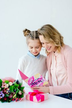 cheerful mother and daughter reading i love you mom greeting postcard together, mothers day concept