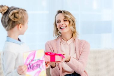 daughter presenting gift box to laughing mother at home on happy mothers day