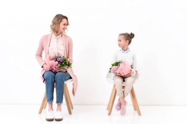 mother and daughter sitting on chairs with bouquets of flowers, happy mothers day concept