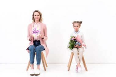 mother and daughter sitting on chairs and looking at camera on happy mothers day