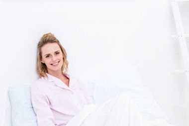beautiful woman lying in bed in morning and looking at camera