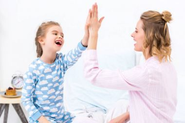 mother and daughter giving high five at home