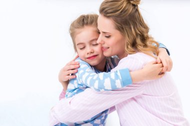 tender mother and daughter hugging at home