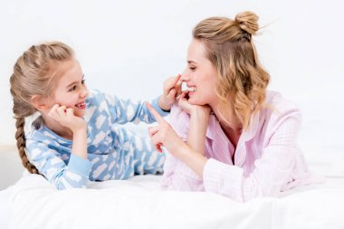 mother and daughter having fun and touching noses with fingers at home