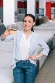 usmívající se žena bok zobrazeno kreditní karty v rukou v obchodu s nábytkem s uspořádány matrace