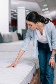 portrét ženy dotýká ortopedické matraci v obchodě nábytek