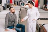 Fotografie selektiven Fokus der männlichen Kunden und Verkäufer im weißen Kittel im Möbelgeschäft mit arrangierten Matratzen hinter