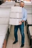 Muž, který držel hromadu skládací matrace v rukou v obchodu s nábytkem