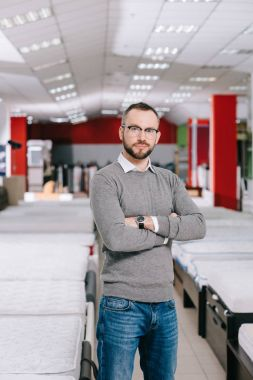 portrait of male customer in eyeglasses in furniture shop with arranged mattresses