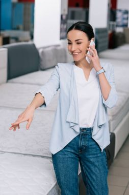 smiling woman talking on smartphone while choosing mattress in furniture store
