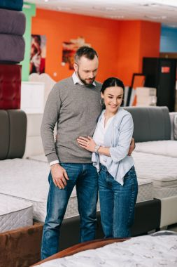 couple hugging while choosing mattress together in furniture shop